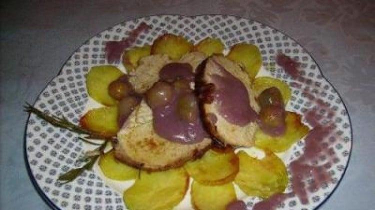 Arrosto di maiale su un letto di patate con salsa al vino e uva