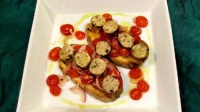 Crostoni alla salsiccia di pesce su insalatina di pomodoro datterino e cipolla Tropea