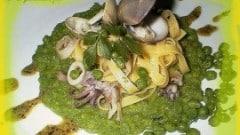 Tagliatelle con calamaretti e vongole su crema di piselli e pesto